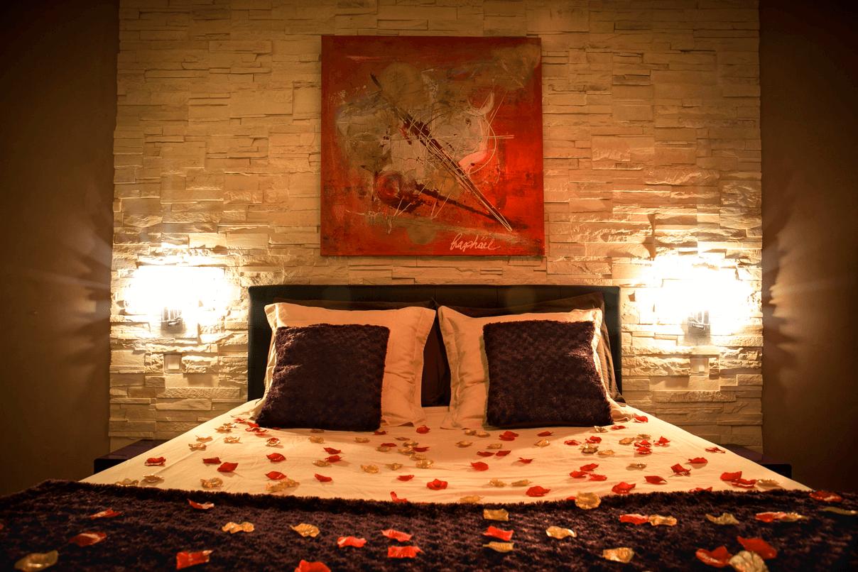 Grand lit confortable avec pétale de rose dans la Suite Romantique et spa votre appartement tous confort en Location privée APPART SPA 21 de Dijon votre appartement privé de luxe, spa et sauna